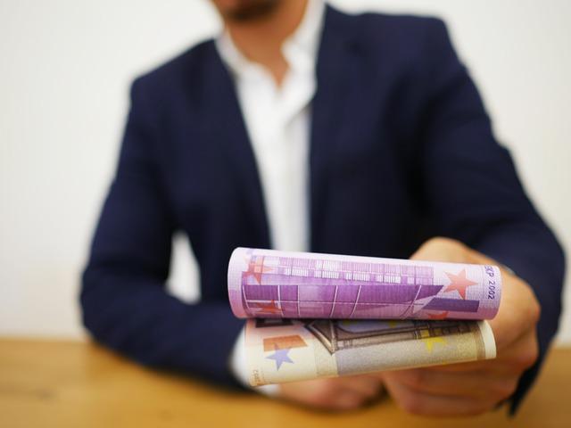 Mann gibt Geldscheine
