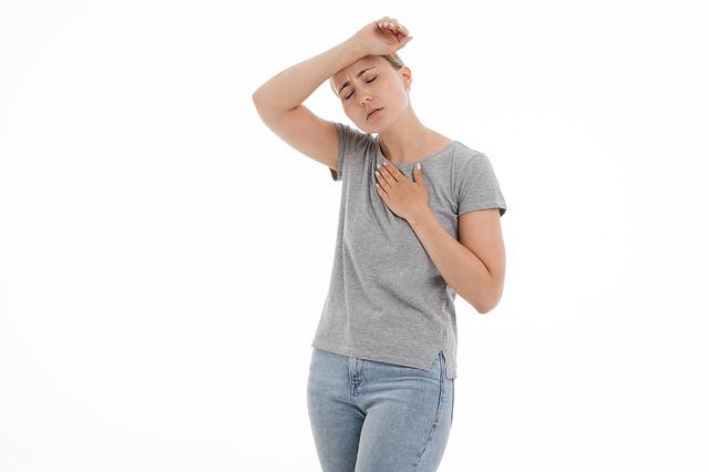 Frau hält sich Hand vor Stirn und Brust