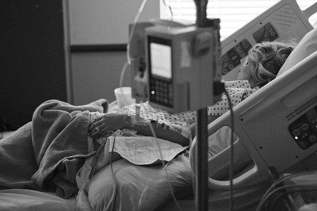 Frau mit Zugängen liegt in Krankenhausbett mit