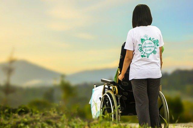 Junge Frau mit Rollstuhl vor sich schaut zum Horizont